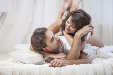 Couple man and woman lay cuddling on the bed at home