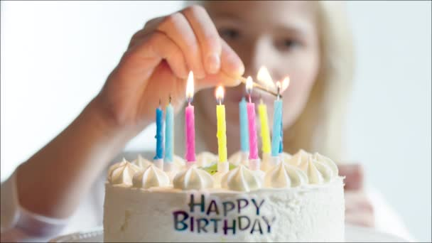 Fiatal nő gyertyagyújtás a boldog születésnapi torta
