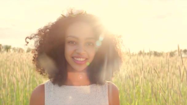Blízko mladé dívky při západu slunce v květinové věnec