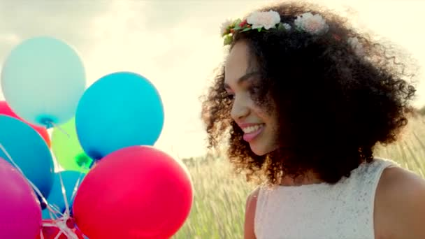 Young girl wearing flower wreath with colour balloons in sunset