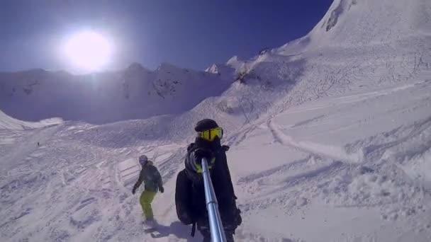 Mann fährt auf Snowboard mit Selfie-GoPro-Stick in der Hand