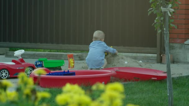 Fiú játszik az autó egy homokozó