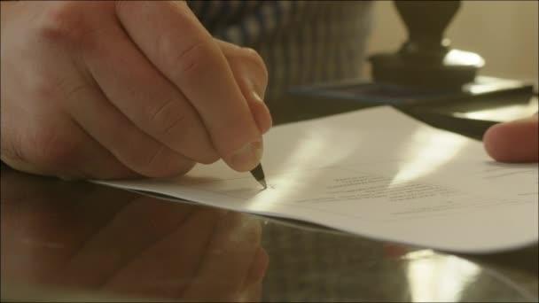 Muž, podepsání smlouvy a nastavování razítka