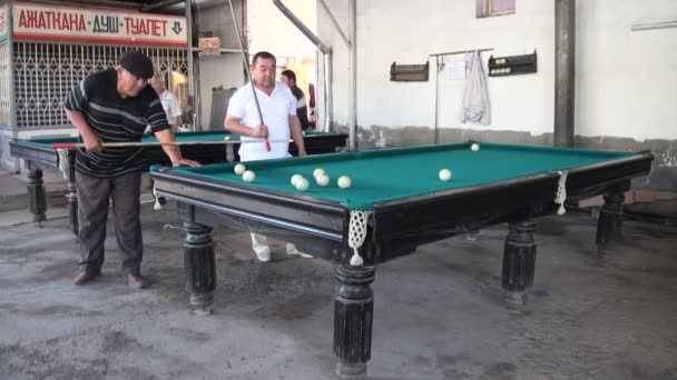 Men play billiards in the bazaar.