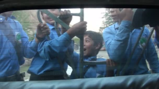 Schoolboys travel on the back of a van