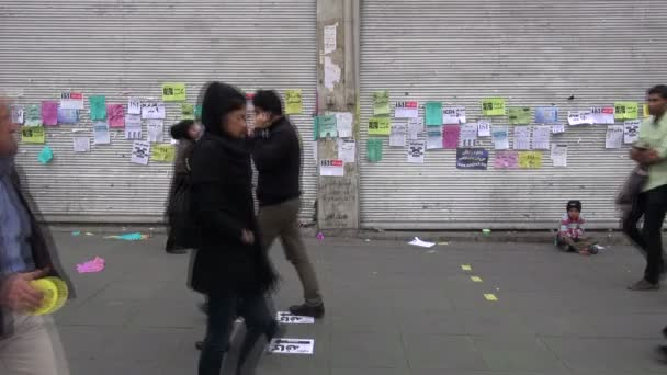 People walk past a young beggar
