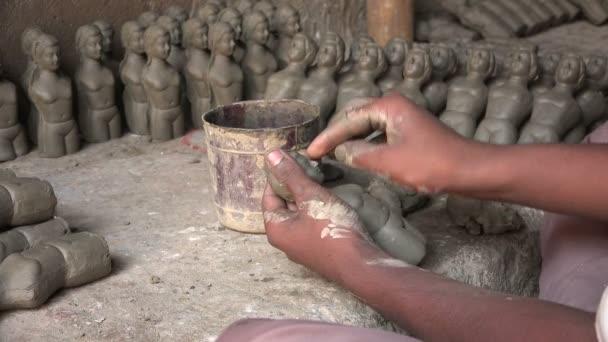 An artist makes clay dolls