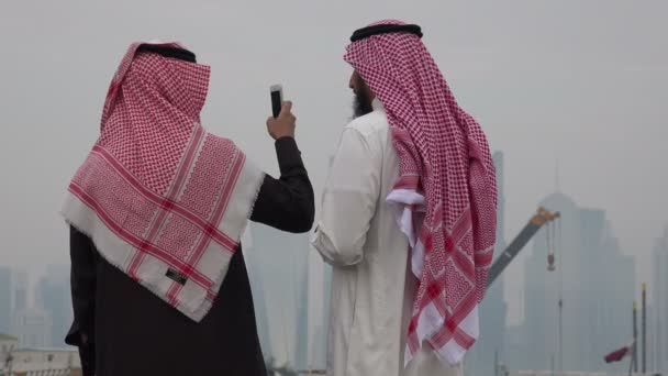 Two men take pictures of the Doha skyline