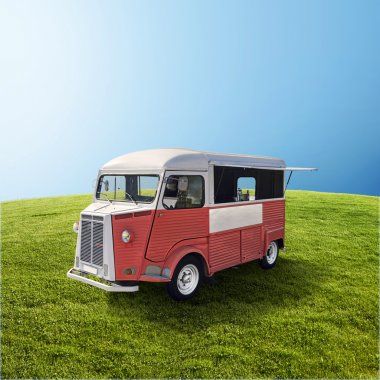 Red food truck on the green field