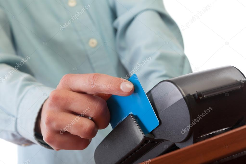 Human hand with credit card swipe through terminal for sale.
