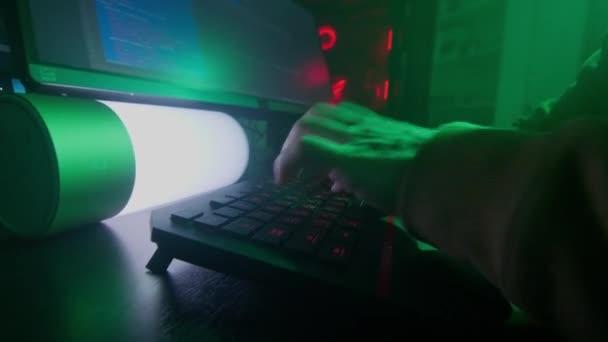 Anonymní osoba v bílé masce pracuje na počítači, vstupní kód, píše velmi rychle na klávesnici, kontroluje informace, kódování, studium, programování, hacking