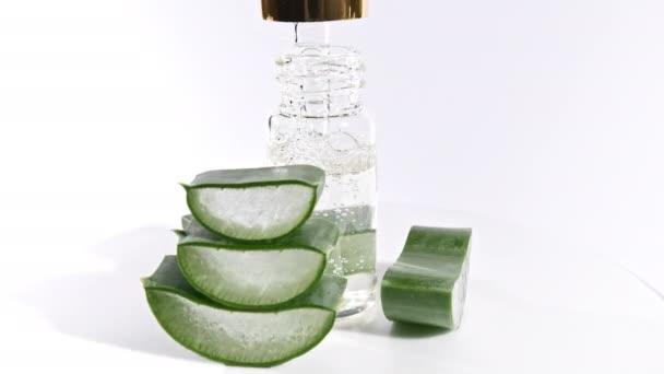 Pohybová rotace nakrájených plátků Aloe Very.Kosmetická pipeta s kapkami oleje Aloe Vera detailní záběr. Přírodní lékařská rostlina. Organická kosmetika, alternativní medicína.