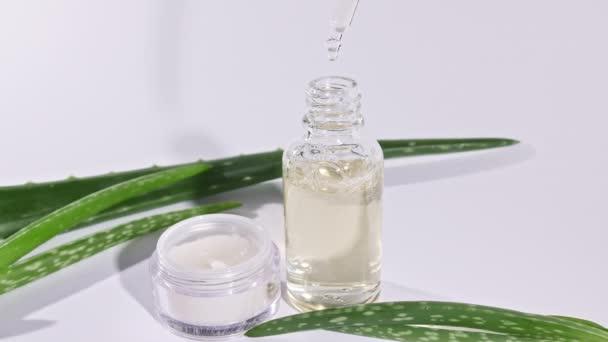 Üvegpalack Aloe Vera olajjal. Aloe Vera kivonaton alapuló kozmetikumok. Fehér arckrémes üveg. Bőr- és testápolás fehér alapon.