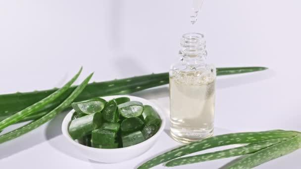 Üvegpalack Aloe Vera olajjal. Közelkép Aloe Vera szeletelt szelet. Természetes orvosi növény. Organikus kozmetikumok, alternatív gyógyászat.