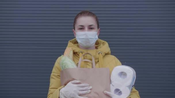 Maskierte Frau mit Einkäufen im Geschäft.
