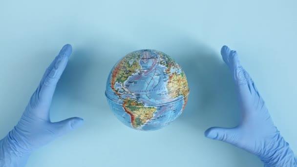 Lékaři ruce v lékařských rukavicích drží, chránit zeměkouli s rukama. Světová epidemie Nebezpečí. Ochrana životního prostředí, zachránit planetu, mír a virus