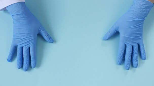 Doctors hands in medical gloves making shape of heart on blue background with copy space.