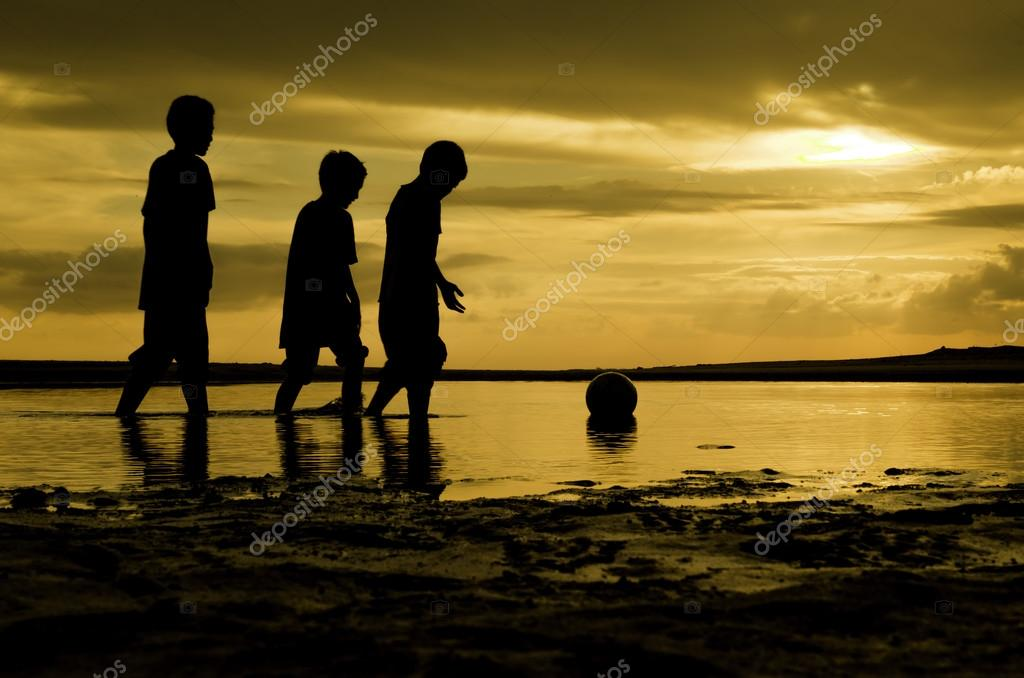 Image silhoutte  three boys walking toward the ball on water. sunset sunrise and reflection on water