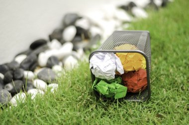 colured crumpled paper on garbage bin on green grass