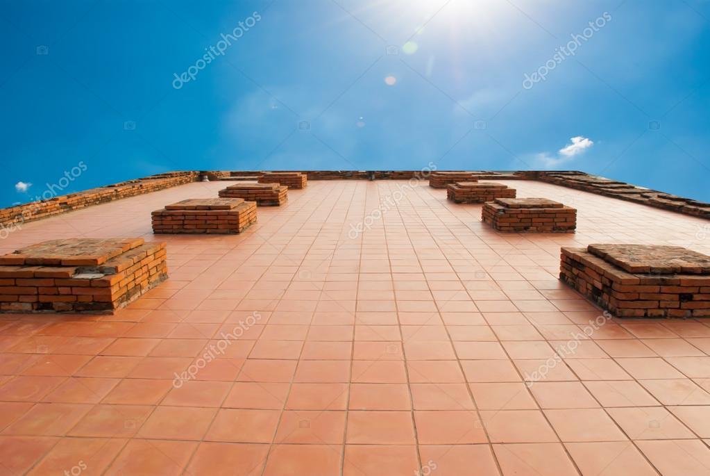 Il rosso piastrelle pavimento con mattoni e cielo blu sfondo u2014 foto