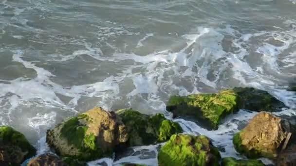 Hullámok zuhannak a sziklákra.