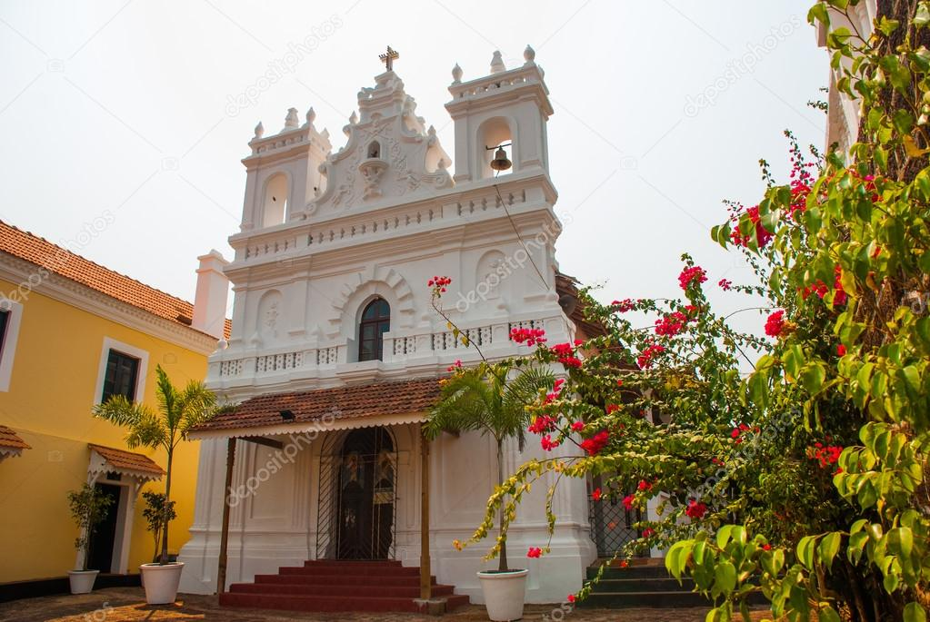 Fort Tiracol. Catholic Cathedral on the background of red flowers. Goa. India