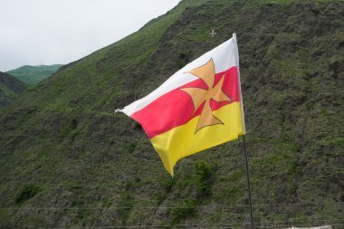 Alan flag flutters in the wind.Color white, red with yellow cross in the middle.The Caucasus.Russia