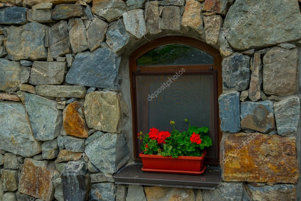 The monastery of stone.A window on stone wall background.Red flowers in a pot.Caucasus.Russia.