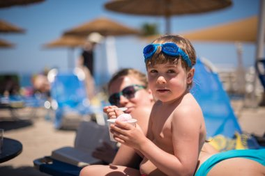 Little girl having ice creams at the outdoor swimming pool