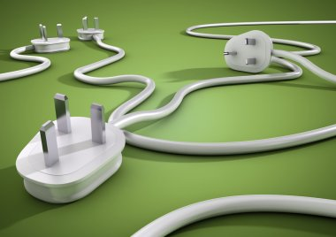 Electical cables and plugs lay on a green smooth surface and overlap each other. Concept for electricity and power usage by consumers.