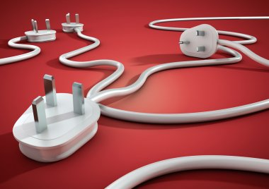 Electical cables and plugs lay on a red smooth surface and overlap each other. Concept for electricity and power usage by consumers.