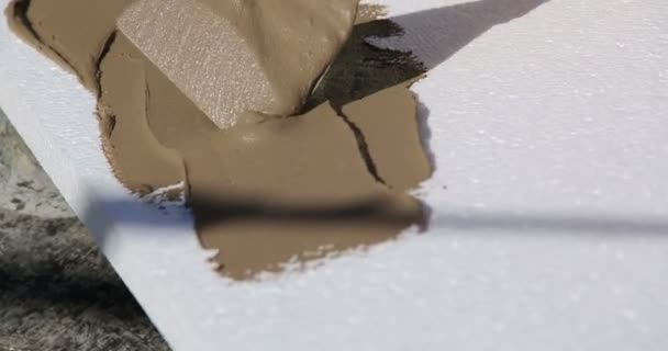Construction. Man inflicts mortar on styrofoam. Close-up.