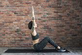 Fotografie tetovaná ženská dělá cvičení doma, sportovní žena cvičí jógu