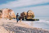 Fotografie Man spielt mit Labrador Hund am Strand