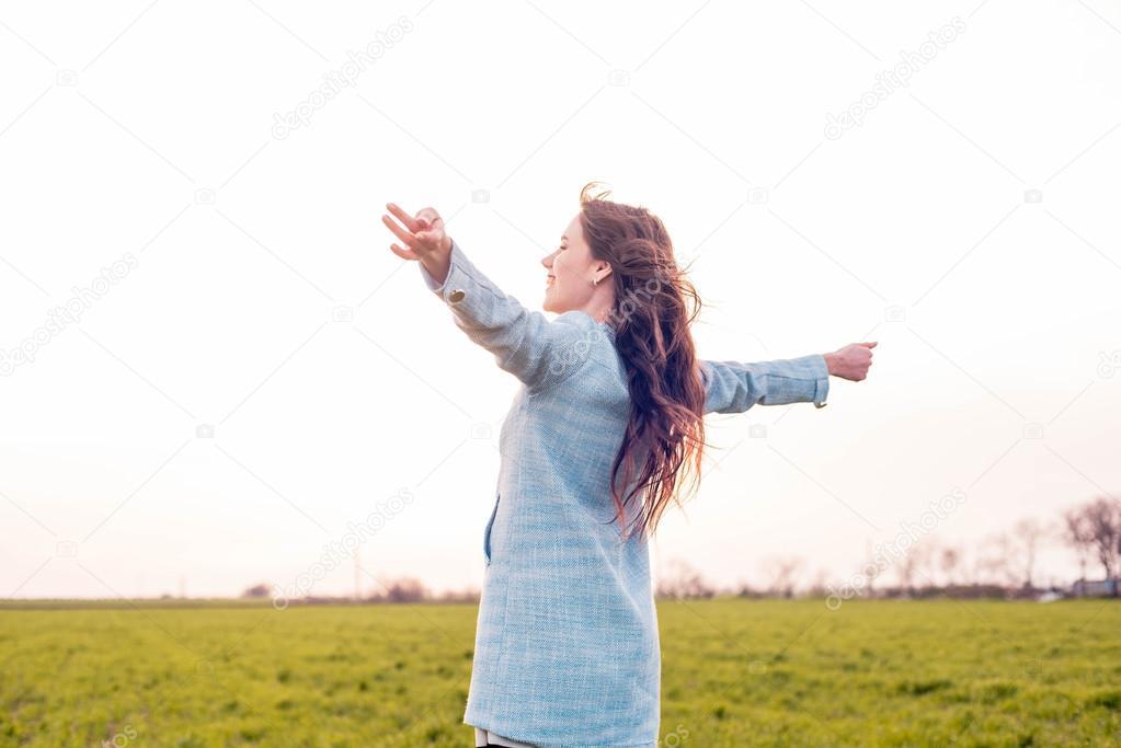 free happy female in field enjoying the sunset