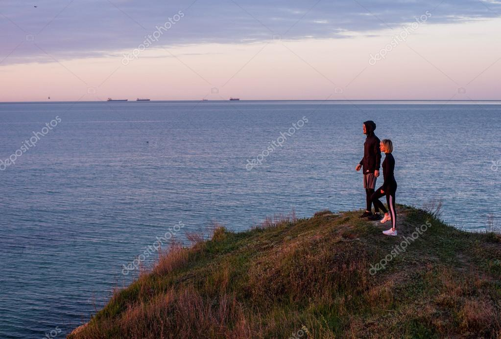 runners standing on the cliff above the sea