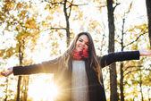 junge glückliche Frau mit jubelnden Händen im Park. Weibchen genießen Herbstsonne