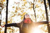 Fotografie Junge, glückliche Frau mit jubelnden Hände im Park. Weibchen, die Herbstsonne genießen