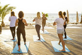 Photo group of young females practicing yoga on the seaside during the sunrise