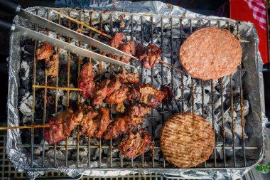 Different types of meat are cooked on the grill