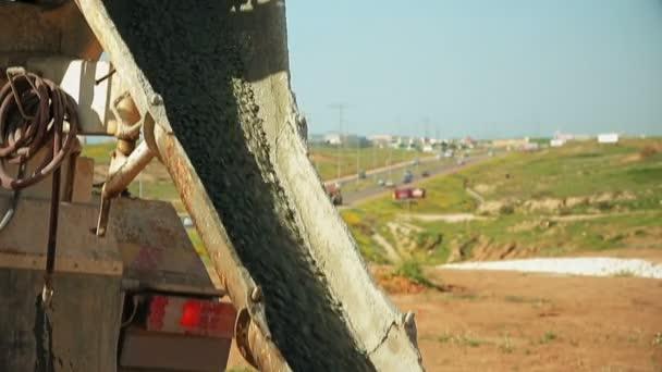 Bauarbeiter gießen Beton von Betonmischer-LKW auf Baustelle in ein Erdloch.