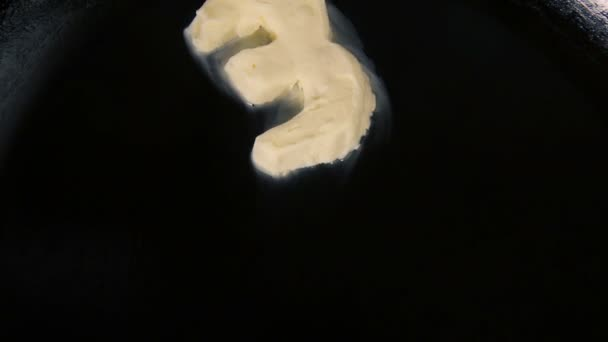 Butter in shape of number 3 melting on hot pan - Close up top view