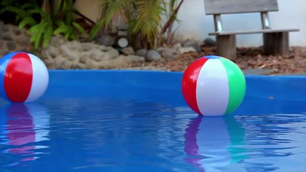 Colorful beach balls floating in pool in slow motion