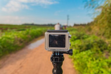GoPro action camera on stick in dirt road at rural area