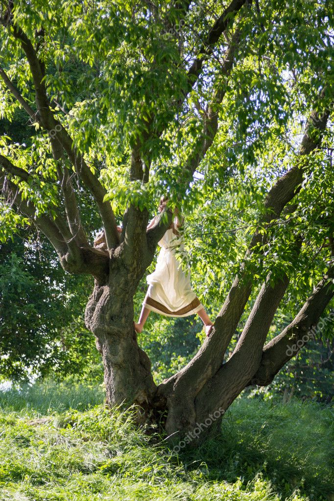 girl climbs a tree in ancient Roman dress