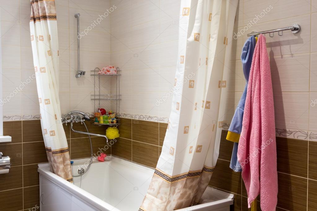 Cuarto de baño con toalla rosa y una bata de baño infantil ...