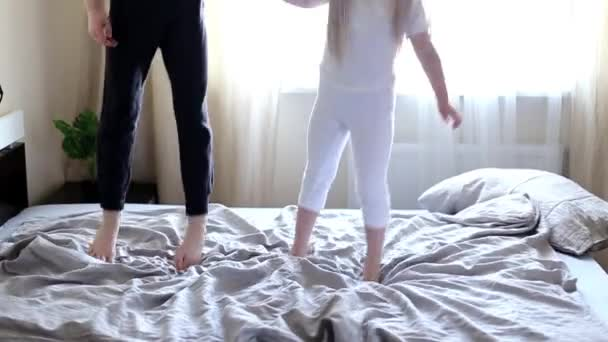 Happy Kids jumping on the bed in the morning. childrens feet on the blanket close