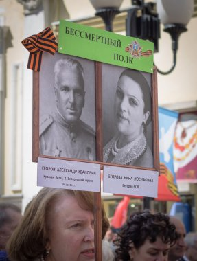 Woman holds sign with pictures of her family dead in the World War II