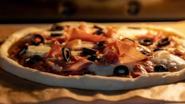 Timelapse of classic Italian pizza with prosciutto baking in an oven.  Trucking camera motion