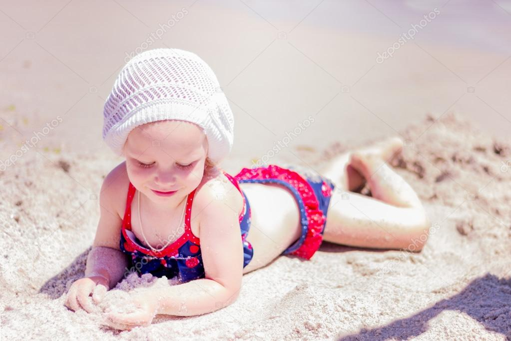 Beautiful little girl lying on the beach